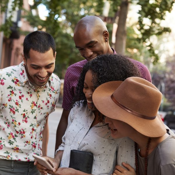Group Of Friends In City Looking At Photo On Mobile Phone