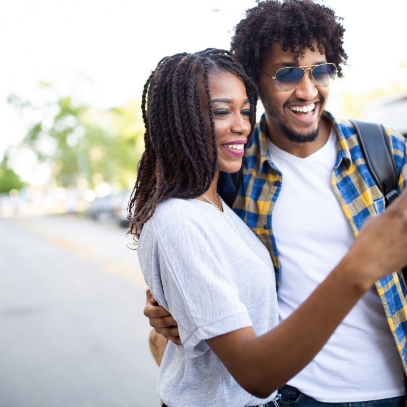 Young couple taking a selfie and having fun outdoors